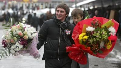 Men give flowers to women for International Women's Day